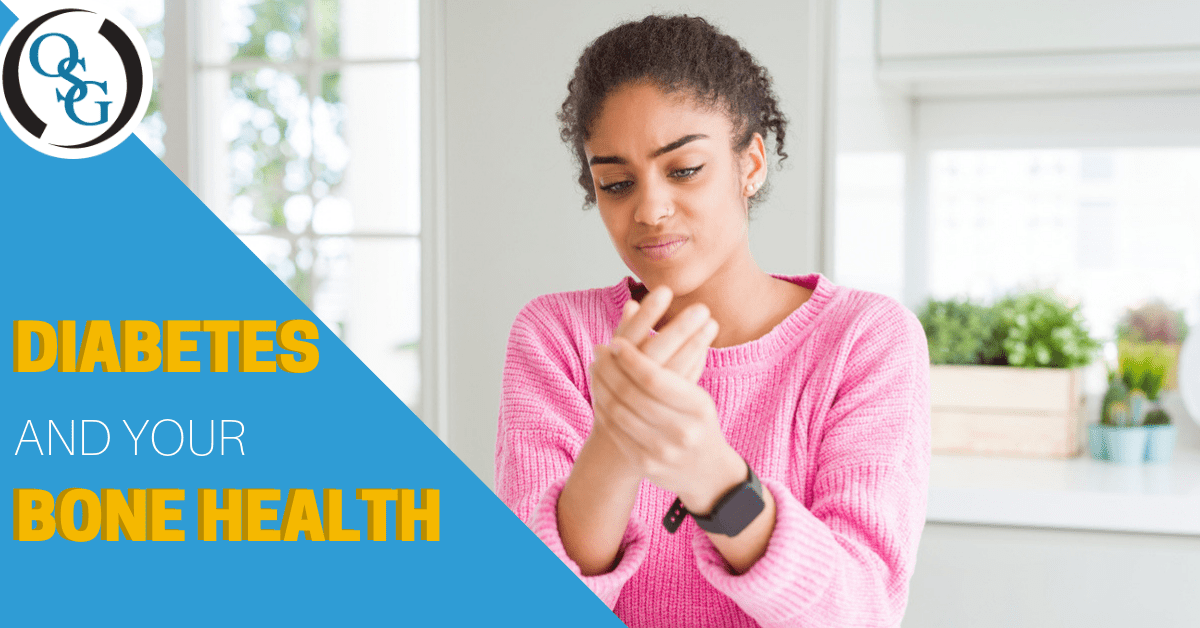 african american woman in pink sweater holding her hand in pain wearing a smart watch