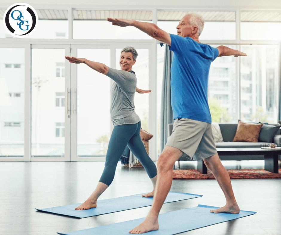 man and woman doing warrior pose on yoga mats