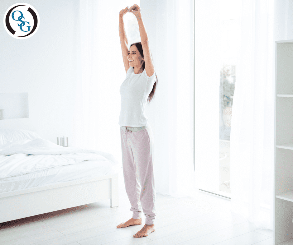 woman standing and stretching with arms raised above her head in bedroom