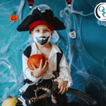 Young boy dressed as a pirate for Halloween and wearing a face mask