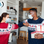 Two people wearing masks and holiday sweaters greeting each other by touching elbows
