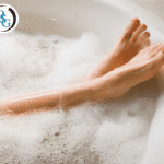 A woman's feet relaxed in a bathtub with soap