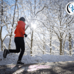 Woman jogging on a pathway through a park during winter