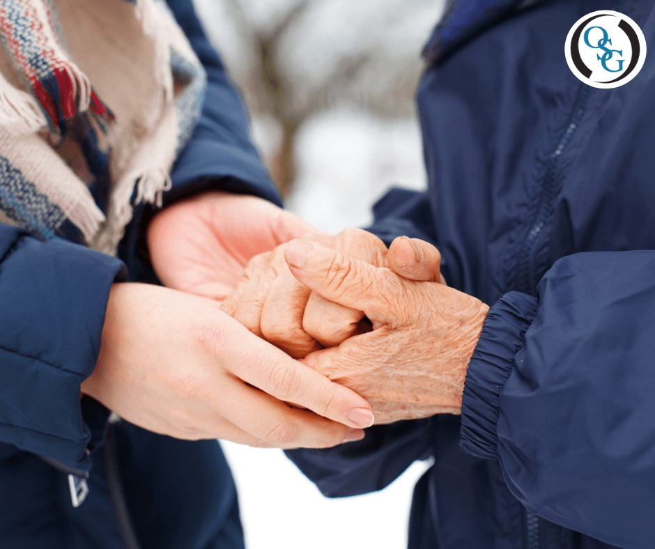 A close up of an elderly couples hands holding each other outside during winter
