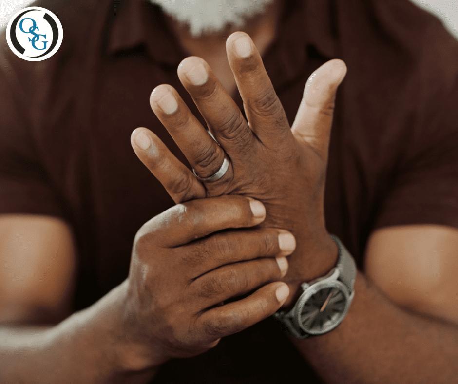 Elderly man grabbing at his hands in discomfort