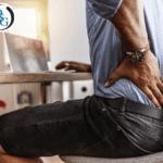 A man grabbing at his back in pain while at his desk