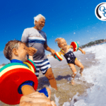 A grandfather and his two young grandchildren playing at the beach by the water