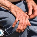 An elderly man grabbing at his knee in pain
